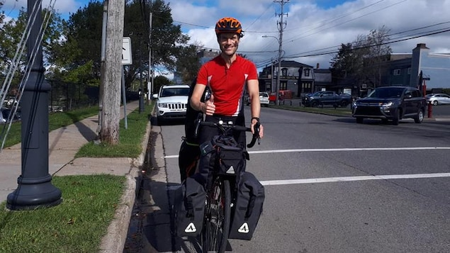 Adrian House sur sa bicyclette dans une rue résidentielle faisant un signe d'approbation du pouce.