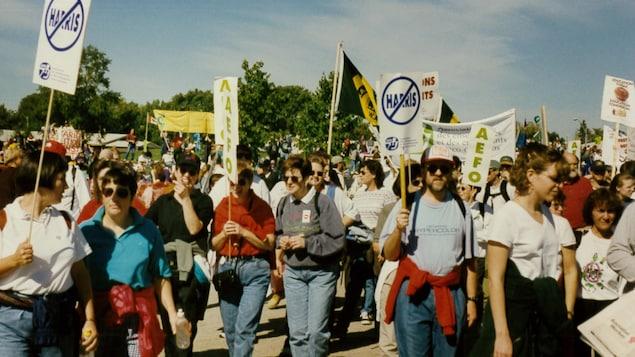 Des enseignants manifestent dehors avec des pancartes.