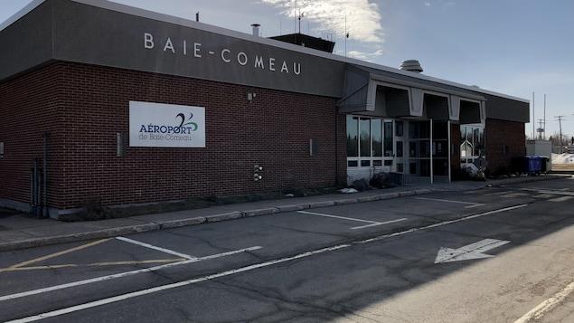 Le bâtiment de l'aéroport en brique brune sous un soleil radieux.