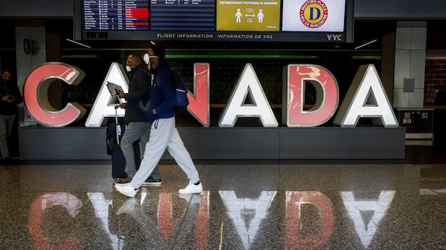 Deux hommes marchent dans un couloir de l'Aéroport de Calgary.