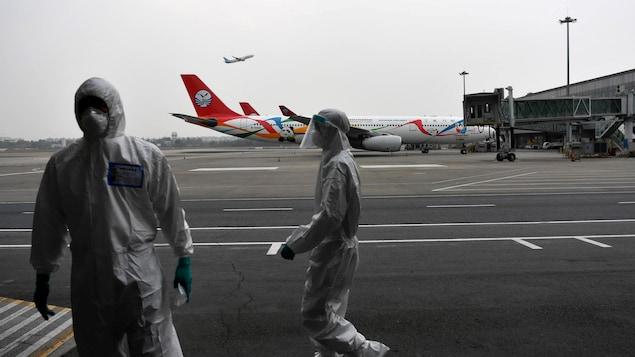 Deux hommes en combinaison et masqués sur le tarmac d'un aéroport.