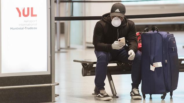 Un homme masqué et ganté attend sur un banc près d'une valise.