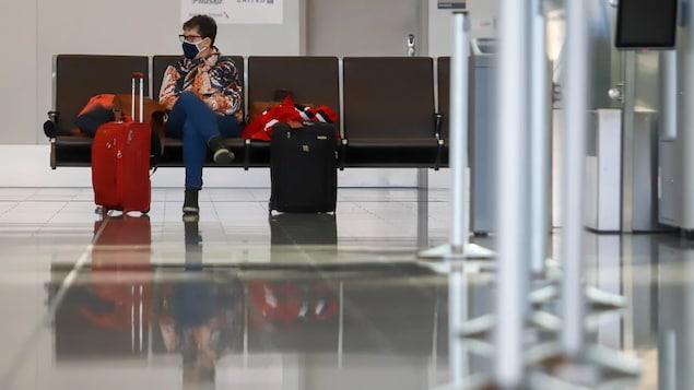 Un passager assis à l'aéroport international de Calgary, en pleine pandémie mondiale de la COVID-19.