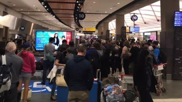Des centaines de personnes attendent leurs bagages.