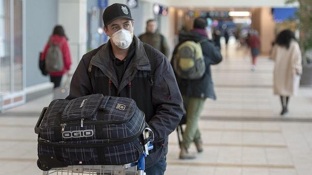 Un homme portant un masque pousse un chariot à bagages à l'intérieur de l'aéroport.