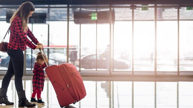 Une mère et sa fillette poussent leur valise dans un aéroport.