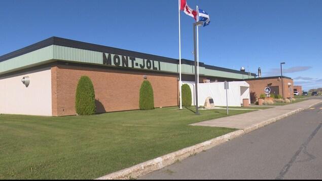 Enseigne et édifice de l'aéroport de Mont-Joli en été, les drapeaux du Québec et du Canada flottent au vent devant l'édifice.