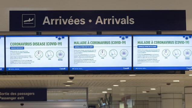 Des messages liés à la pandémie de COVID-19 diffusés sur des écrans à l'aéroport de Montréal.