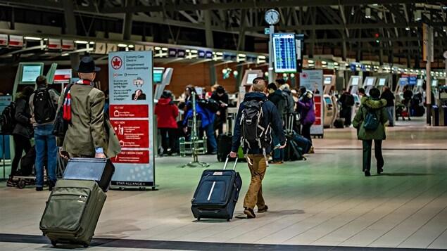 Des voyageurs à l'aéroport d'Ottawa.