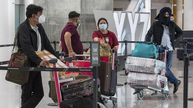 Quatre passagers indiens attendent avec leurs bagages.