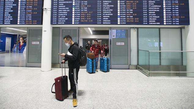 Un homme porte un masque à son arrivée à l'aéroport Pearson de Toronto.