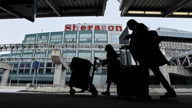 Deux voyageurs, en ombre chinoise, passent devant la façade de l'hôtel Sheraton.