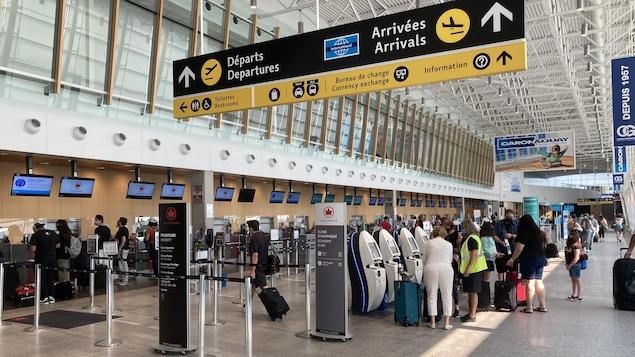 Vue d'ensemble du hall d'embarquement de l'aéroport de Québec. On y voit des guichets et des gens avec des valises.