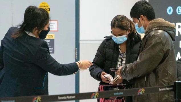 مسافران يقدّمان وثلئق إلى موظّف في مطار.