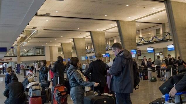 Des passagers font la file pour enregistrer leurs bagages à l'aéroport international Pierre-Elliott-Trudeau de Montréal.