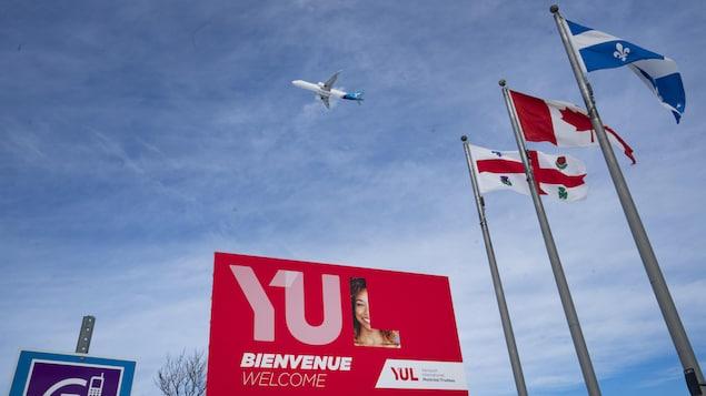Des drapeaux, une grande pancarte sur laquelle est écrit YUL et un avion dans le ciel.
