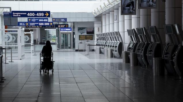 Une femme marche seule dans un corridor de l'aéroport.