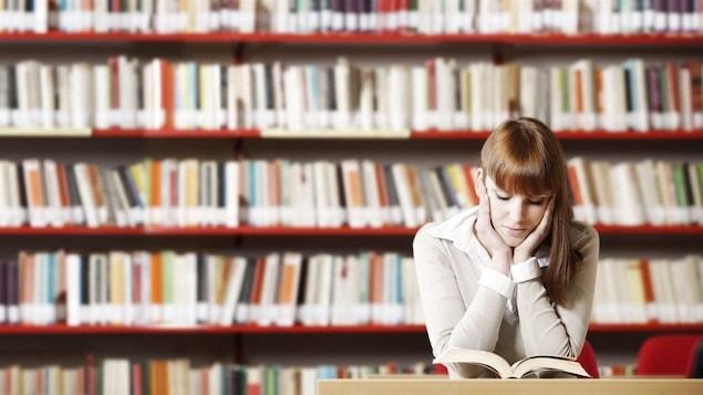 Une femme lit dans une bibliohtèque. Des étagères remplies de livres sont derrière elle