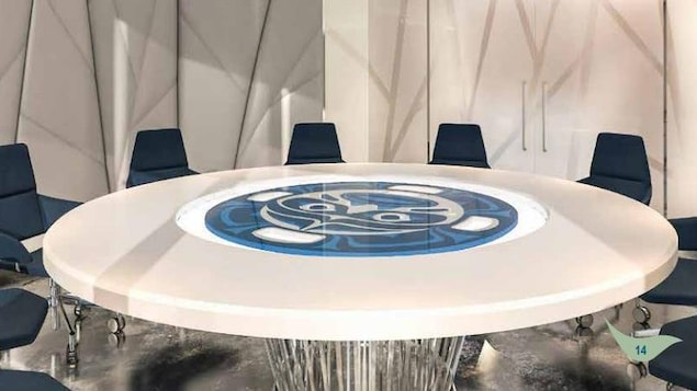 Une grande table ronde blanche et bleue dans un décors capitonné épuré.