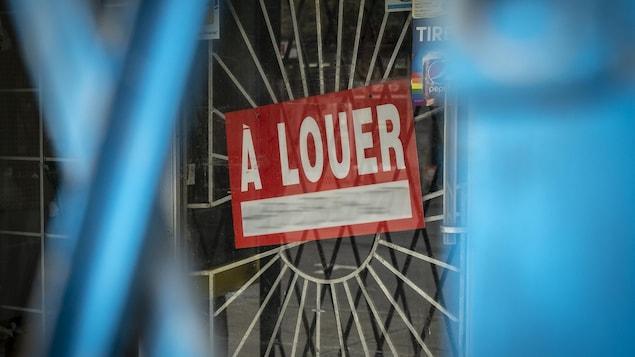 Une affiche « À louer » est posée dans la fenêtre d'un bâtiment.