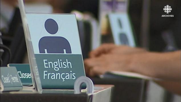 Affichette sur un comptoir indiquant que le service se fait en anglais et en français.