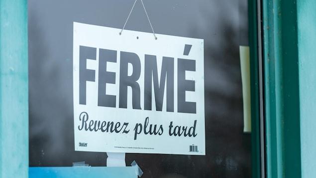 Une affiche sur laquelle ont peut lire « fermé » et « revenez plus tard » dans la porte d'un commerce non identifié.