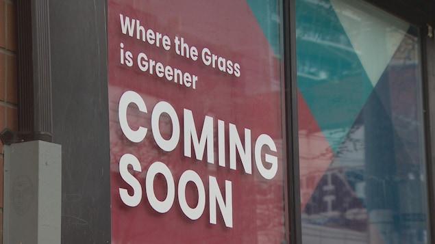 Une grande affiche rouge, collée dans une vitrine, qui indique qu'un magasin de cannabis sera bientôt ouvert à cet endroit.