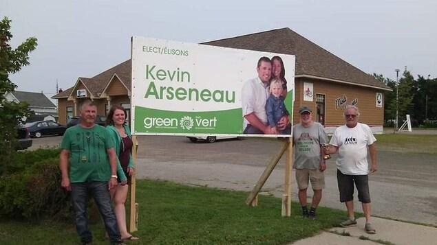 Quatre personnes se tiennent près d'une pancarte électorale du candidat Kevin Arseneau du Parti vert.