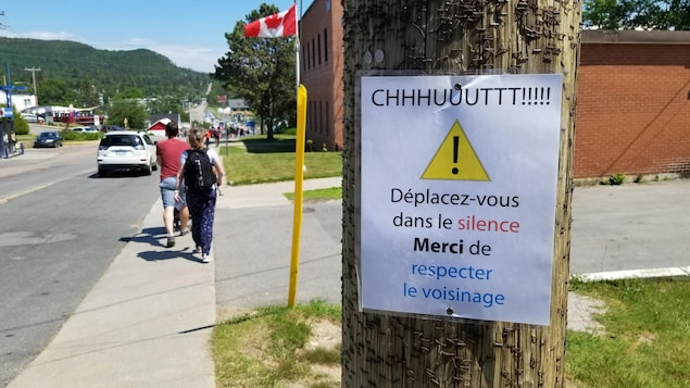 Une pancarte sur laquelle on peut lire « Chut! Déplacez-vous dans le silence. Merci de respecter le voisinage. » est clouée sur un poteau de téléphone.