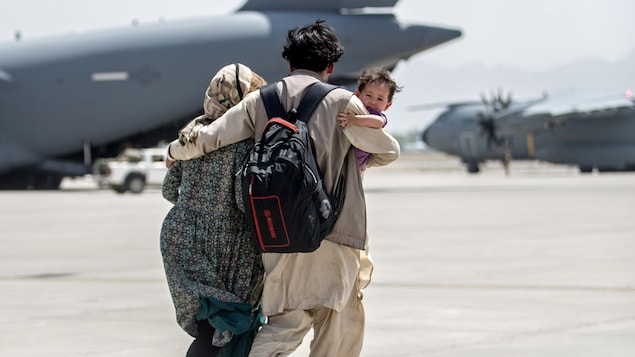 Un couple avec un enfant dans les bras du père sur le tarmac d'un aéroport.