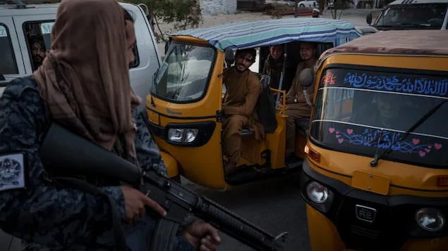 Afghan drivers and passengers stuck in a traffic jam look at Taliban fighters riding in the back of a pickup truck in Kabul, Afghanistan, Monday, Sept. 20, 2021. An Afghan-Canadian woman is asking Ottawa for help getting her fiancé — a former Afghan air force pilot — out of an internment camp.