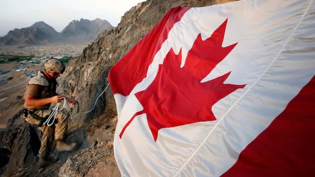 A Canadian soldier hangs a flag on a mountainside near the operating base at Ma'sum Ghar in 2007.