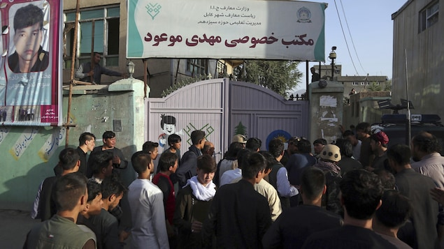 Des dizaines de personnes sont rassemblées devant les portes fermées d'un immeuble.