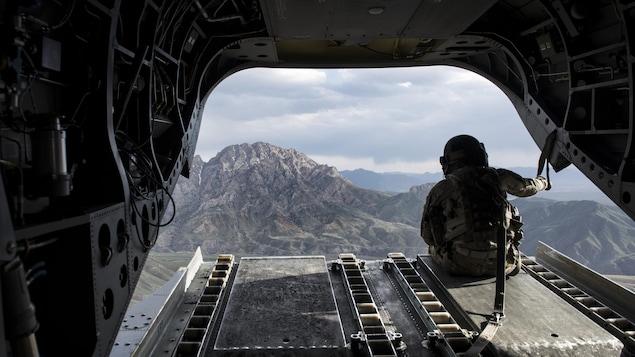 Un militaire américain regarde des montagnes à partir d'un hélicoptère Chinook.