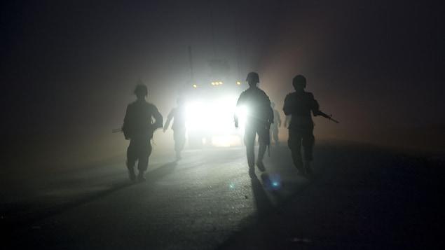 La silhouette de soldats vue devant les phares d'un véhicule.