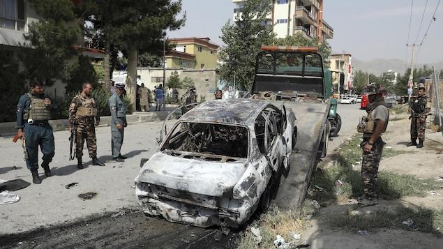 Des membres du personnel de sécurité afghan inspectent un véhicule endommagé.