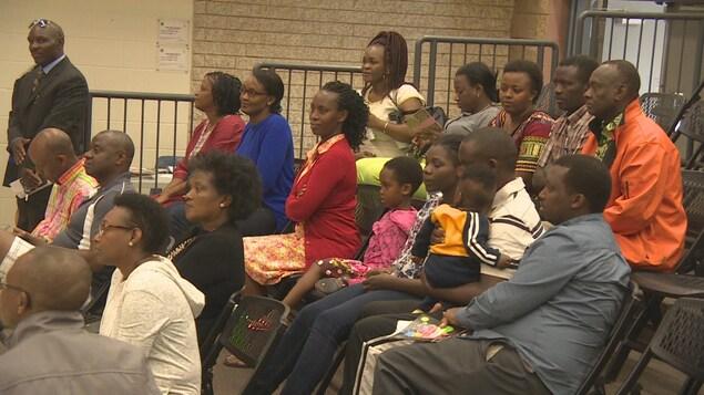 Des membres de la Communauté des Africains francophones de la Saskatchewan sont assis dans une salle lors d'un discours