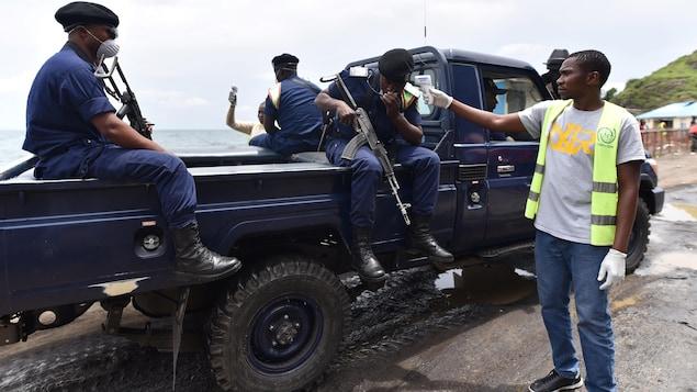 Trois policiers sont assis à l'arrière d'un camion et un homme prend la température de l'un d'eux.