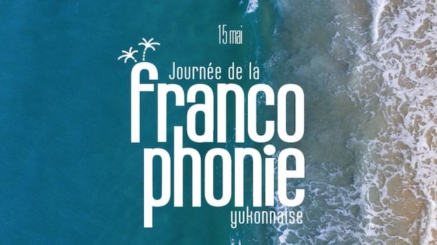 Une inscription annonçant la journée de la francophonie yukonnaise au-dessus d'une plage.