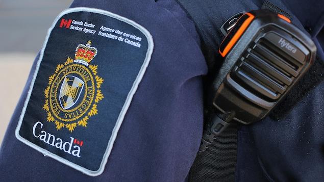 Écusson d'un agent de l'Agence des services frontaliers du Canada, qui porte également un émetteur-récepteur portatif.