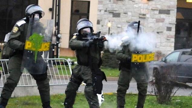 L'agent Burelle, au milieu de ses collègues, utilise son arme d'impact.