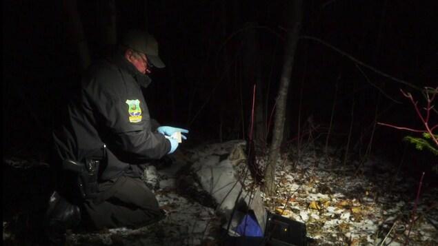 On voit un agent de la faune agenouillé près d'une carcasse, la nuit, éclairé par un projecteur. De la neige recouvre le sol.