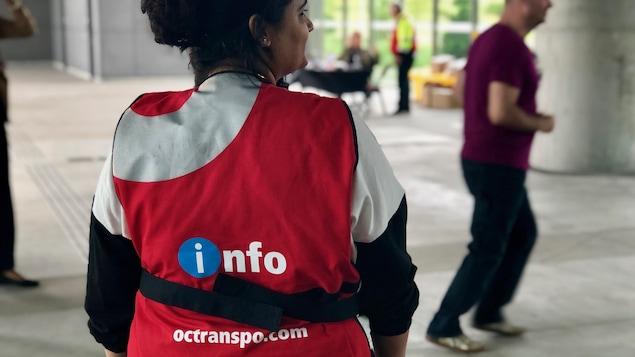 Une agente d'information d'OC Transpo, de dos, dans une station de la ligne de la Confédération.
