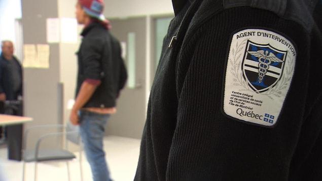 un jeune homme dans une institution avec un agent, dont l'écusson indique qu'il est un agent d'intervention.