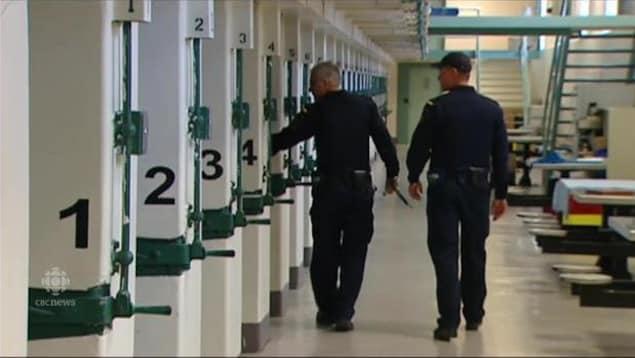 Deux agents correctionnels marchent dans un couloir.