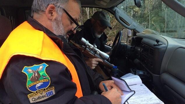 L'agent complète un constat d'infraction d'un chasseur.