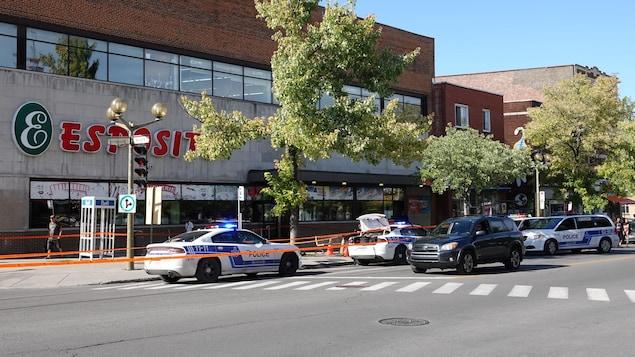 Plusieurs véhicules de police et des rubans de sécurité devant un commerce dans les rues de Montréal.