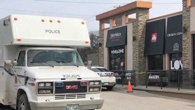Deux véhicules du Service de police de Winnipeg à l'extérieur d'un restaurant où une femme a été agressée.