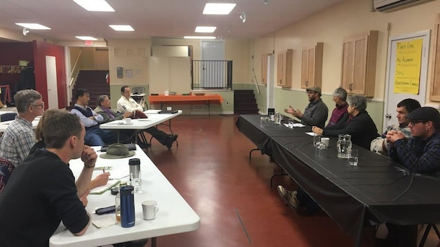 Une dizaine de personnes dans une salle écoutent un conférencier.