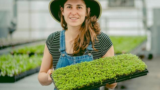 Une jeune agricultrice présente ses étalages.